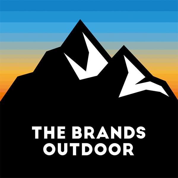 Una montagna nera, un tramonto come sfondo e, in bianco, il logo The Brands Outdoor che si staglia sulla montagna stessa.