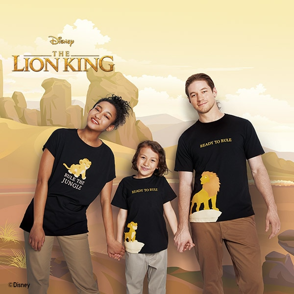 A family pose in The Lion King Collection T-shirts, featuring printed slogans including 'Rule the Jungle' and 'Ready to Rule'