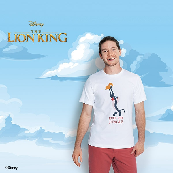 A man wears a white The Lion King Collection T-shirt featuring a print of Raifiki holding Simba aloft