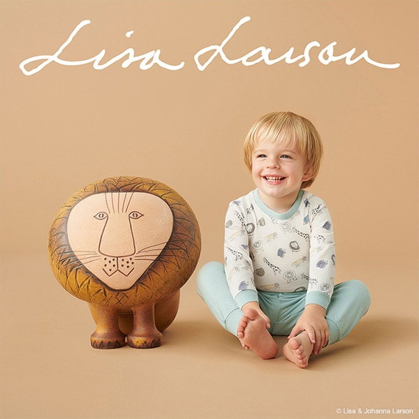 A young boy in white and blue Lisa Larson UT pyjamas smiles next to one of Larson's popular lion sculptures.