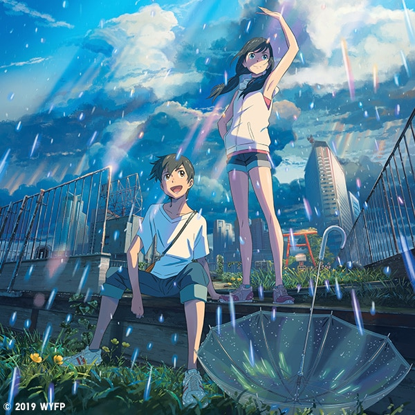 Un giovane uomo e una giovane donna in piedi sotto la pioggia sullo sfondo di una città.