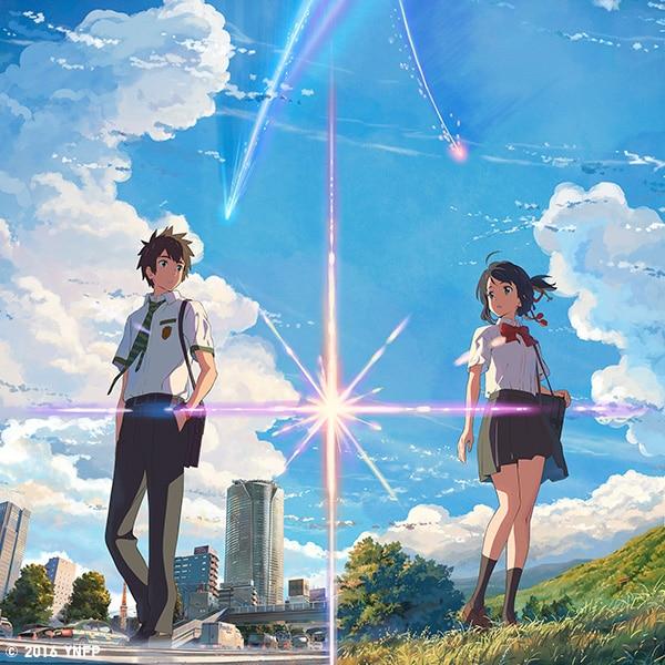 Un giovane uomo e una giovane donna in piedi, sullo sfondo di una città e un campo.