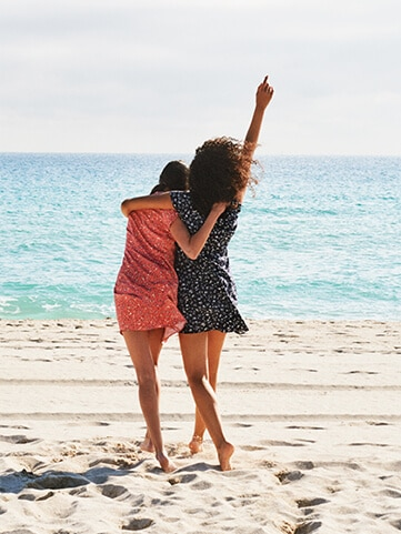 Two women on the beach facing away from the camera to the sea