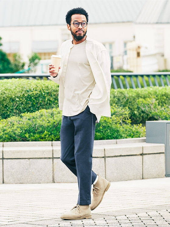 A man walking along a street with a coffee cup in hand