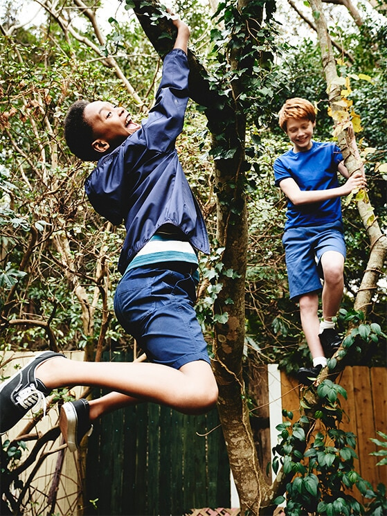 Two boys swinging from a tree branch