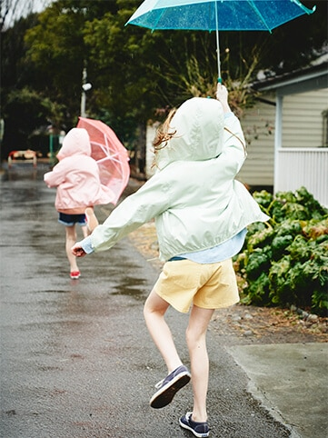 Two girls chasing after each other on a rainy street