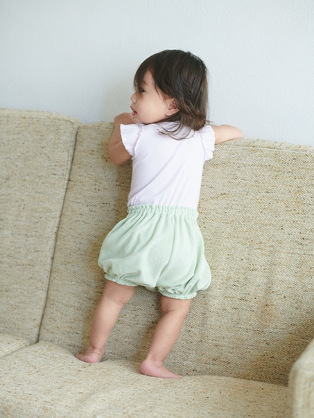 toddler standing on a sofa